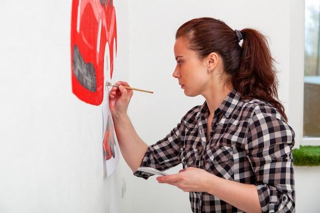 Zakończenie młodej kobiety artysta i matka chłopiec rysuje czerwonego samochód w lekkim dziecięcym pokoju
