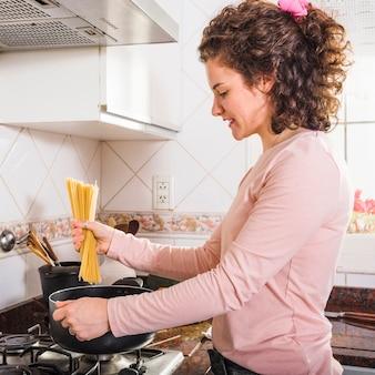 Zakończenie młodej kobiety narządzania spaghetti w kuchni