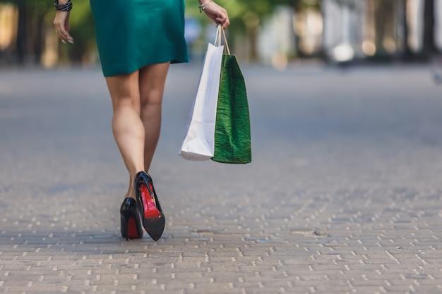 Zakończenie młodej kobiety przewożenia torba na zakupy podczas gdy chodzący wzdłuż ulicy