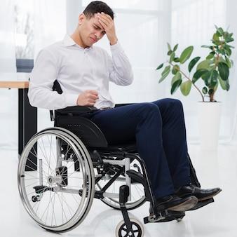 Zakończenie młody biznesmen siedzi na wózku inwalidzkim ma ból głowy