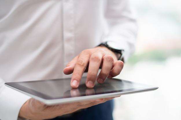 Zakończenie młody biznesmen używa cyfrową pastylkę