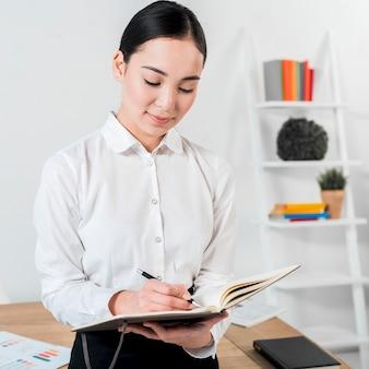 Zakończenie młody bizneswoman pisze w dzienniczku z piórem