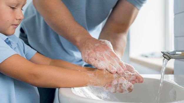 Zakończenie młody chłopiec mycia rąk z ojcem