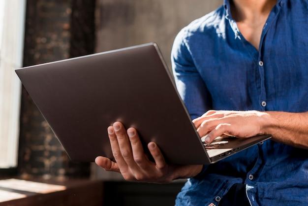 Zakończenie młody człowiek używa laptop w ręce