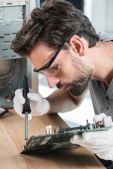 Zakończenie młody męski technik pracuje na komputerowej płycie głównej