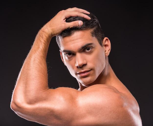 Zakończenie młody mięśniowy mężczyzna patrzeje kamerę.