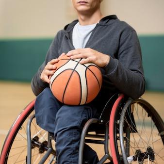 Zakończenie młody niepełnosprawny mężczyzna trzyma piłkę