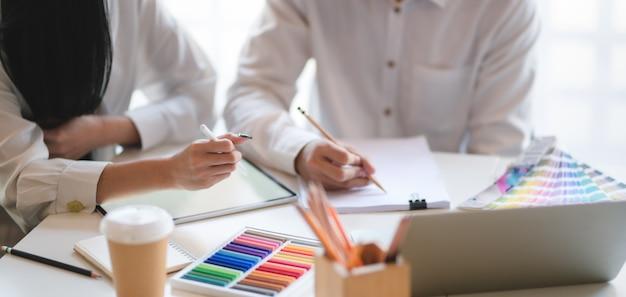 Zakończenie młody profesjonalny projektant grafik zespołowych planuje ich projekt w nowożytnym biurze wpólnie