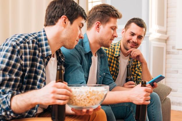 Zakończenie młodzi człowiecy siedzi na kanapie patrzeje smartphone