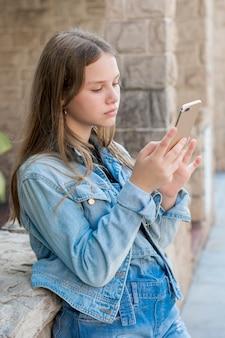 Zakończenie nastoletnia dziewczyna w drelichu używać mądrze telefon przy outdoors