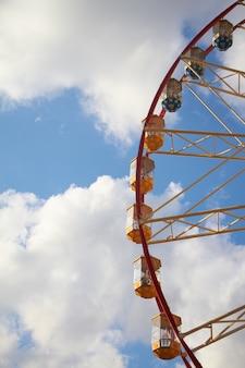Zakończenie nowożytny ferris koło przeciw niebieskiemu niebu i bielowi chmurnieje, zabawa festiwal