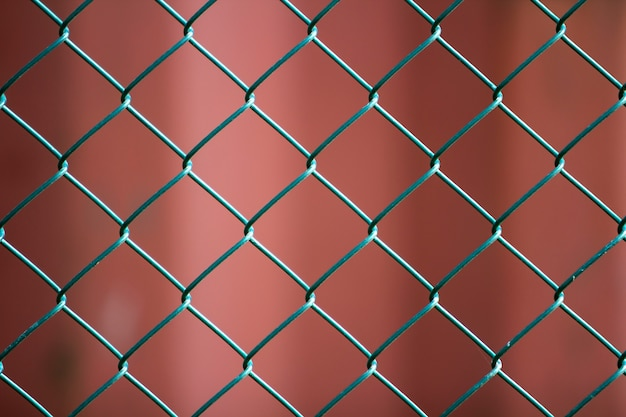 Zakończenie odosobnionego malującego prostego geometrycznego czerni żelaza metalu drucianego łańcuszkowego połączenia ogrodzenia eonu zmrok - czerwona scena. koncepcja ogrodzenia, ochrony i ogrodzenia.