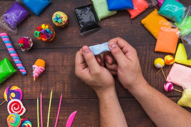 Zakończenie osoba robi tortowi i lollipops z gliną na drewnianym stole
