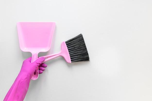 Zakończenie osoba trzyma małą miotłę z purpurowymi rękawiczkami