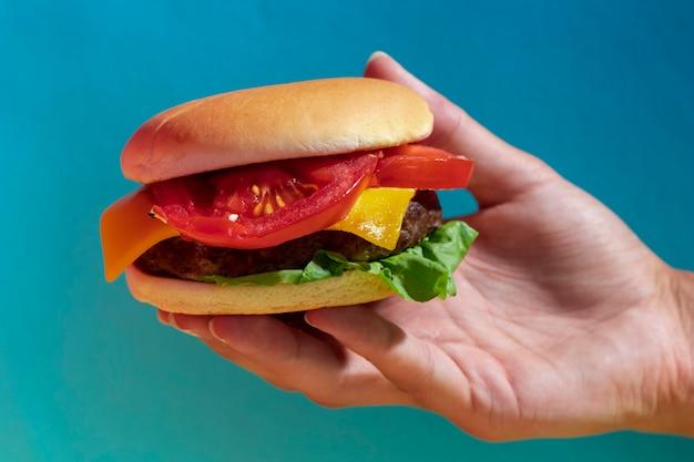 Zakończenie osoba trzyma up smakowitego cheeseburger z błękitnym tłem