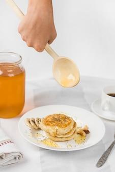 Zakończenie osoby dolewania miód z drewnianą kopyścią na domowej roboty blinie na talerzu