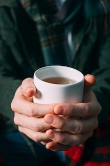 Zakończenie osoby mienia kubek z ciepłym napojem