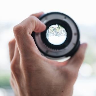Zakończenie osoby ręka pokazuje miasto widok przez cyfrowego obiektywu