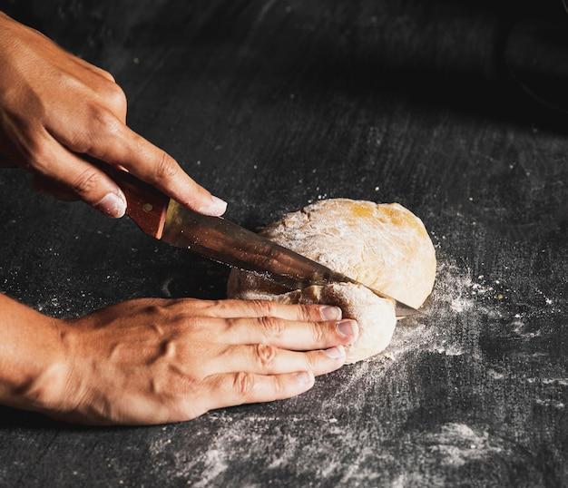 Zakończenie osoby tnący ciasto na czerń stole