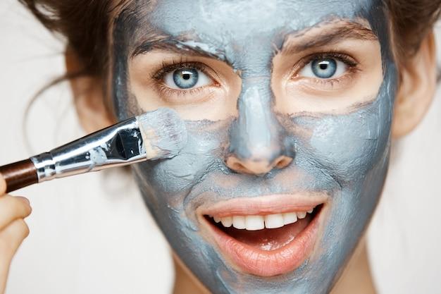 Zakończenie piękna kobieta w włosianych curlers up uśmiecha się nakrycie twarz z mack. zabieg na twarz. kosmetyki kosmetyczne i spa.