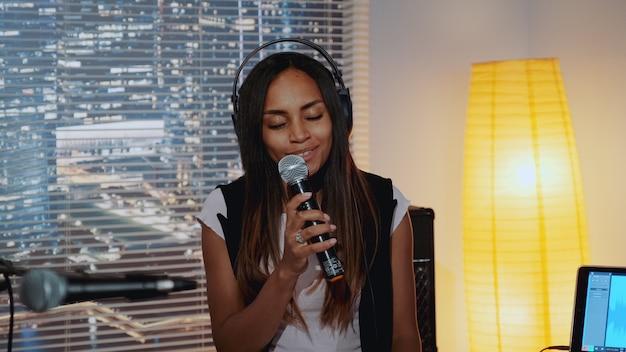 Zakończenie piękna wielorasowa dziewczyna śpiewa w mikrofon i nagrywa piosenkę w domowym studiu
