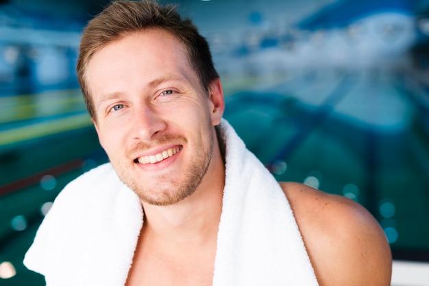 Zakończenie pływaczka pozuje z ręcznikiem na jego ramionach