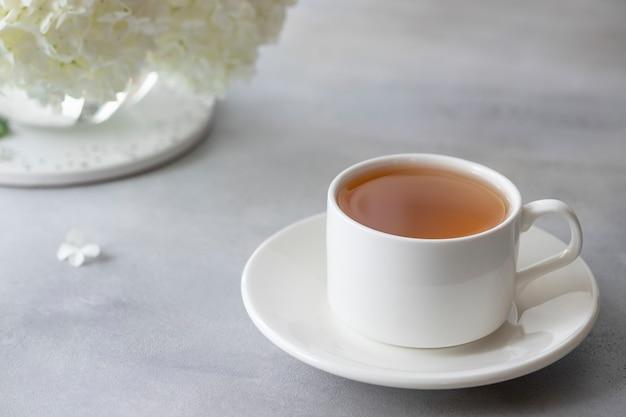Zakończenie porcelanowa filiżanka z ziołową herbatą na rozmytej ścianie biali kwiaty. minimalizm. obraz poziomy. szara betonowa ściana.