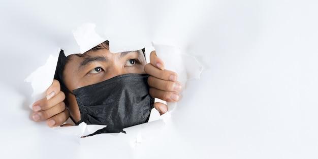 Zakończenie portret jest ubranym ochrony twarzy maskę przeciw koronawirusowi mężczyzna