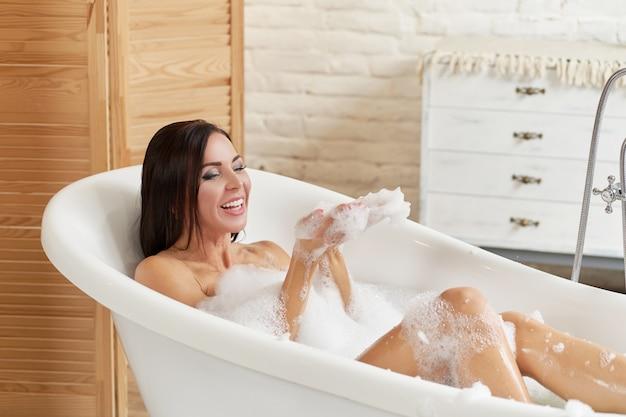 Zakończenie portret kobieta relaksuje w bąbla skąpaniu