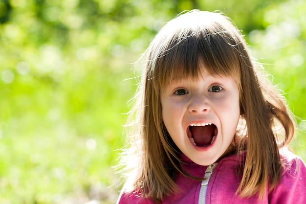 Zakończenie portret mała ładna dziewczyna z krzyczącym wyrazem twarzy