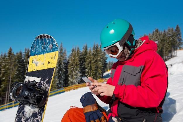 Zakończenie portret męski snowboarder obsiadanie w śniegu, używać jego mądrze telefon podczas gdy odpoczywający w górach