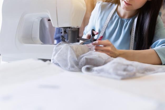 Zakończenie portret młoda indyjska szwaczka lub krawcowa szyje na maszynie do szycia w jej własnym miejscu pracy.