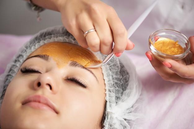 Zakończenie portret piękna dziewczyna w specjalnym kapeluszu na jej głowie stosuje złotą twarzową maskę. kosmetologia sprzętowa.
