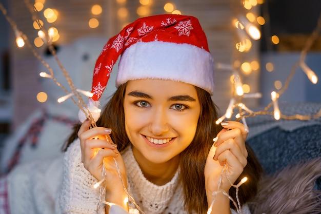 Zakończenie portret roześmiana śliczna młoda kobieta z santa kapeluszem na głowie z girlandami w jej rękach