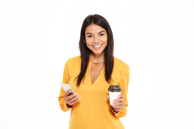 Zakończenie portret szczęśliwa młoda brunetki kobieta w żółtej koszula trzyma filiżankę kawy i telefon komórkowego