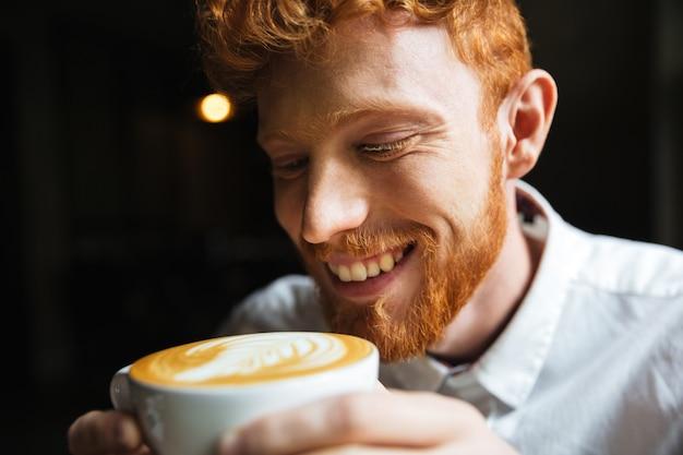 Zakończenie portret uśmiechniętego kędzierzawego rudzielec brodaty mężczyzna kosztuje kawę w filiżance