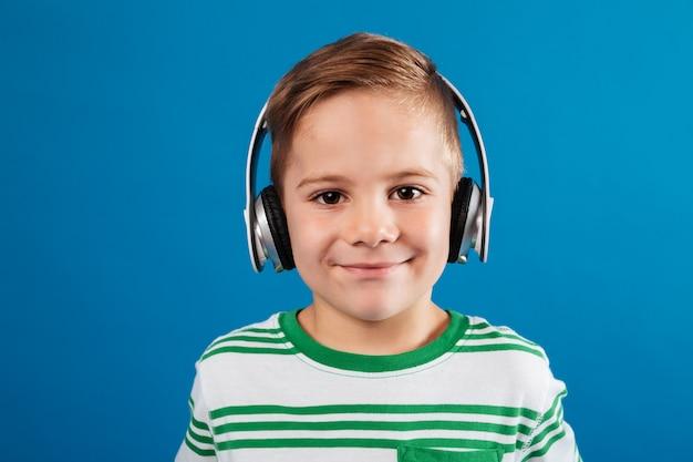 Zakończenie portret uśmiechniętej młodej chłopiec słuchająca muzyka słuchawki