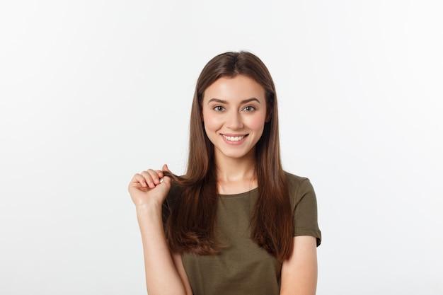 Zakończenie portret yong kobiety przypadkowy portret w pozytywnym widoku, duży uśmiech, piękny model pozuje w studiu nad biel ścianą.