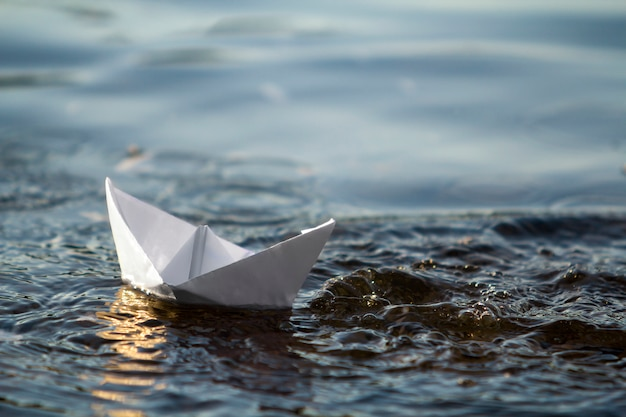Zakończenie prosta mała biała origami papieru łódź unosi się w błękita jasnym rzece lub wodzie morskiej pod jaskrawym lata niebem. pojęcie piękna natury, wolności, marzeń i fantazji.