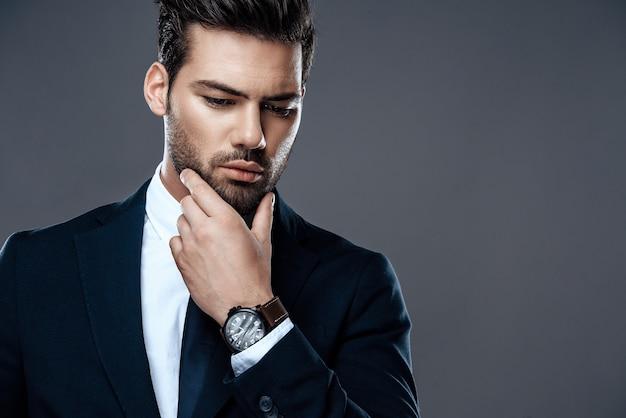 Zakończenie przystojny i pomyślny mężczyzna w drogim kostiumu.