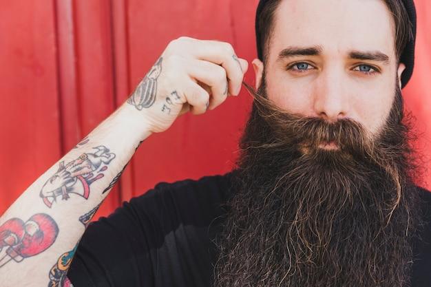 Zakończenie przystojny mężczyzna ciągnie jego wąsy patrzeje kamerę