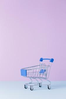 Zakończenie pusty wózek na zakupy przed różowym tłem