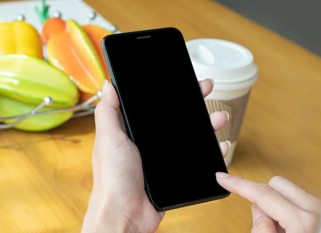 Zakończenie ręka kobieta w domu używać nowożytnego smartphone dla zakupy online.