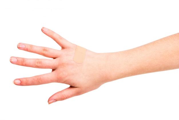 Zakończenie ręka młoda kobieta z adhezyjnym bandażem.