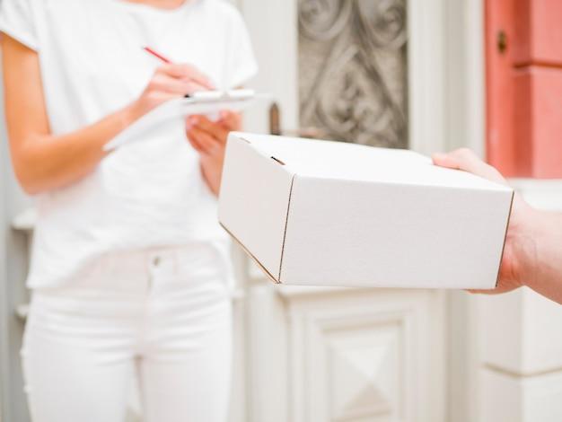 Zakończenie ręka trzyma białego pudełko