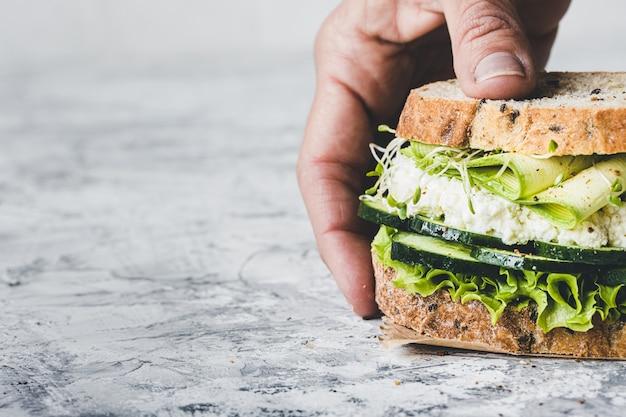 Zakończenie ręka trzyma jarską kanapkę z zielonymi warzywami. sałata, cukinia, lucerna i ogórek. wegańskie jedzenie