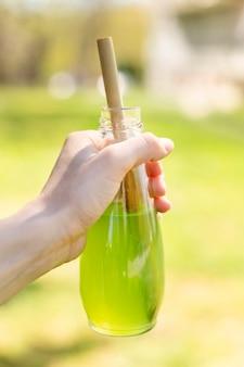 Zakończenie ręka trzyma szklaną butelkę z sokiem i papierową słomą
