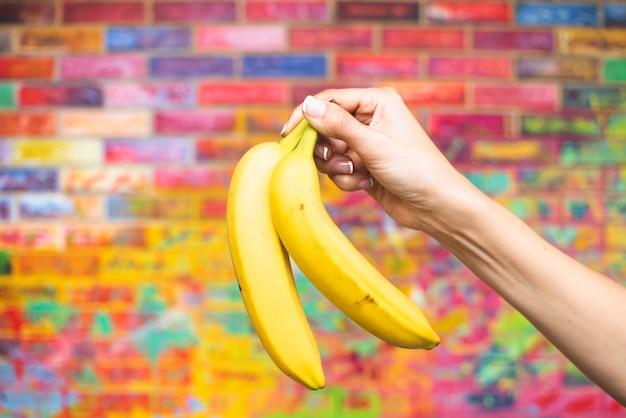 Zakończenie ręka trzyma up banany