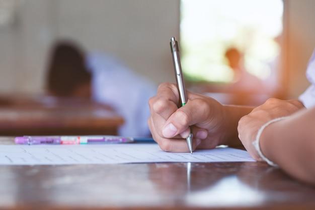 Zakończenie ręka ucznie pisze egzaminie w sala lekcyjnej z stresem