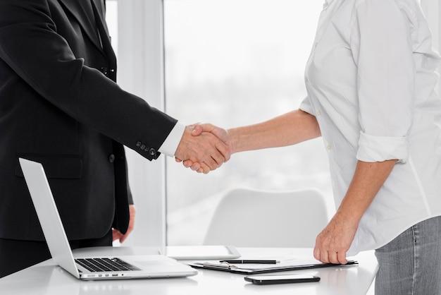Zakończenie ręki biznesowy potrząśnięcie przy biurem